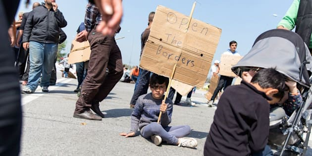 A boy holds a sign on April 4, 2016 on the third day of protest along the highway outside Polykastro, in Central Macedonia, Greece.
