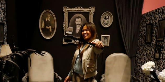 Une femme prend un égoportrait dans une pièce en noir et blanc durant une visite exclusive du Musée des selfies à Glendale en Californie.