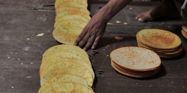 An Indian worker arranges khakra at a food factory.