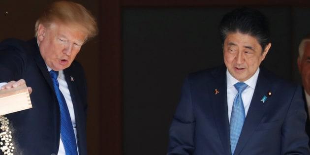 El presidente de EEUU, Donald Trump, y el primer ministro japonés, Shinzo Abe, dando de comer a las carpas japonesas.