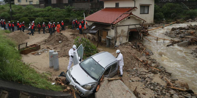 流された車両を調べる広島県警の警察官(手前)ら=7月8日午前、広島市東区馬木