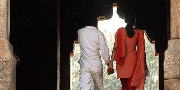 A young Indian couple hold each other's hand as they visit a monument in a park on Valentine's Day.