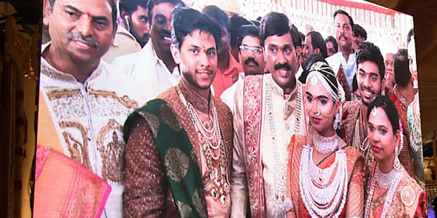 Indian mining tycoon, Gali Janardhan Reddy, (C) is seen on a big screen as he poses with his daughter Bramhani (2R) and son-in-law.