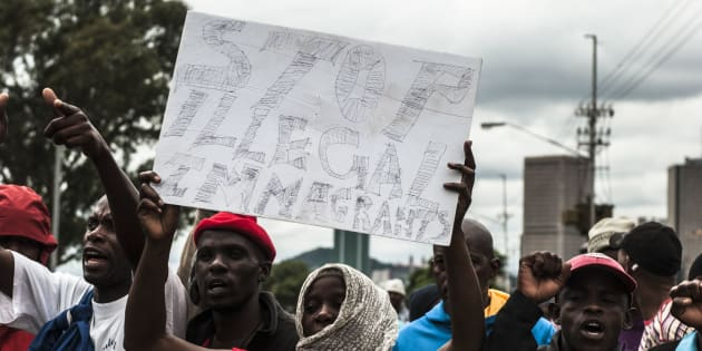 Protesters sing and chant during protest over immigrants in Pretoria on February 24. Police fired rubber bullets and stun grenades to control the situation.