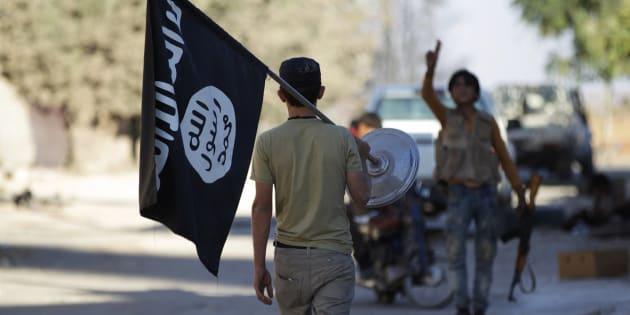 Un rebelde toma la bandera del ISIS después de que los yihadistas escapasen de la localidad de Akhtarin, en Siria, a principios de octubre.