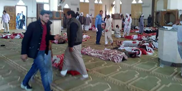 Egyptians walk past bodies following a gun and bombing attack at the Rawda mosque, roughly 40 kilometres west of the North Sinai capital of El-Arish, on November 24, 2017.