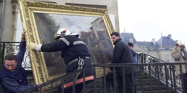 Des pompiers s'affairent pour évacuer des tableaux, en janvier 2003, au château de Lunéville.