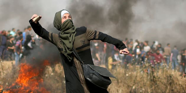Una joven palestina lanza piedras a las tropas de Israel, esta mañana, en la frontera de Gaza.