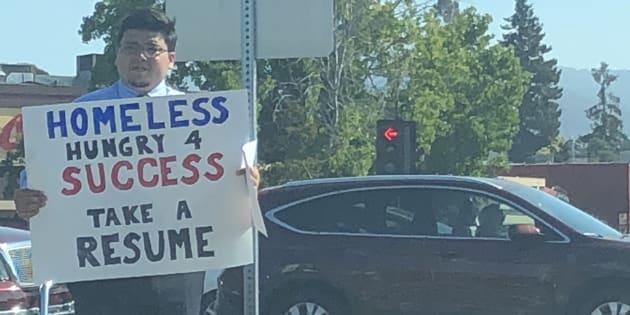 「ホームレスは成功を望んでいます。履歴書を受け取ってください」と書かれた紙を掲げるカサレスさん