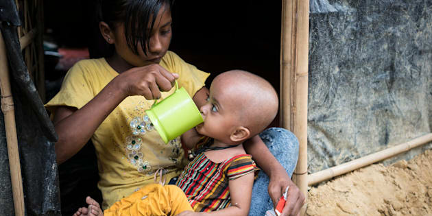 On 20 November 2017 in Bangladesh, severely malnourished Rohingya refugee 10-month-old Atica, sips water from a mug held by her sister, 11-year-old Musaddeka, after eating ready-to-use therapeutic food, at their family's shelter in the Moinerghona refugee camp in Cox's Bazar district. Because of scarce resources and harsh living conditions in the camp, Atica has gotten sick and is now suffering from severe acute malnutrition. After days and weeks on the run from the Myanmar military – spent in the bush without food – many refugees are arriving in the camps severely malnourished. The sisters and their family fled their home and homeland after the military set fire to their village.  Since late August 2017, some 620,000 Rohingya have fled from Myanmar to neighbouring Bangladesh to escape the violence in their homeland. More than half of them are children – many in dire need of vital support. High levels of severe acute malnutrition (SAM) among young children have been found in refugee camps, and urgent nutrition needs have been prioritized for children under aged 5 (including infants), for pregnant and lactating women and for adolescent girls. In order to increase malnutrition treatment and preventive nutrition coverage, a Nutrition Action Week, launched on 15 November and led by UNICEF and the Government, is targeting all children under age 5 for mid-upper arm circumference (MUAC) screenings and referrals, vitamin A supplementation and deworming. On the launch's first day, over 12,100 children 6-59 months of age received vitamin A capsules; more than 8,200 children 24-59 months old were reached with deworming; some 12,840 children were screened for malnutrition; and over 3,500 at-risk children were referred to outpatient treatment programmes. Over the next six months, nearly 17,000 children suffering from severe acute malnutrition are to receive support, and nutrition sector partners plan to cover 70 per cent of the identified needs in makeshift and new