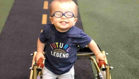 二分脊椎と診断された2歳の赤ちゃん、杖を持って「歩く」