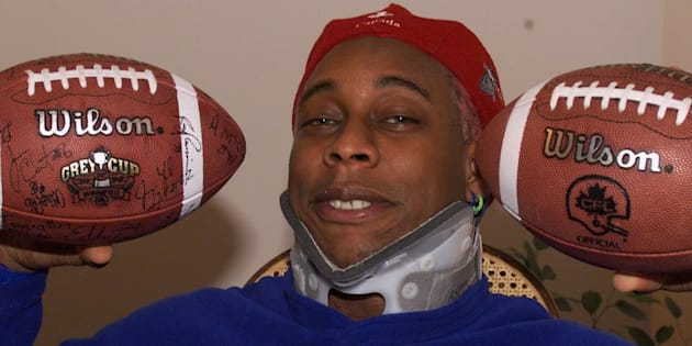 Former Calgary Stampeders linebacker Anthony McClanahan poses wearing a neckbrace and holding up two footballs in Calgary in 1999.