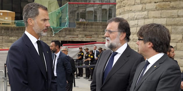 El rey Felipe VI departe con el presidente del Gobierno, Mariano Rajoy, y el presidente de la Generalitat, Carles Puigdemont, antes de la misa de ayer en la Sagrada Familia de Barcelona.