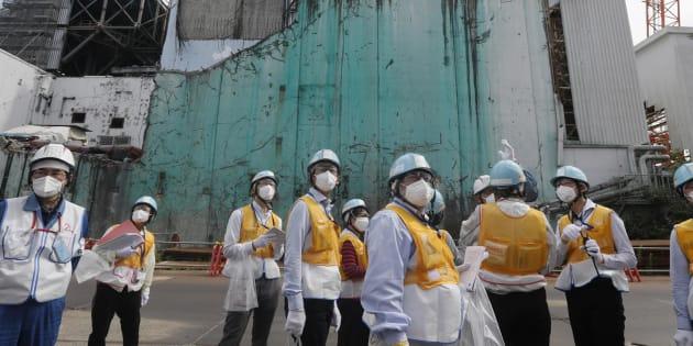 Dans cette photo prise ce 27 juillet, des journalistes étrangers reçoivent des informations sur les travaux de démantèlement entre le réacteur 2 et l'unité 3 (en arrière-plan) à Tokyo Electric Power Company (TEPCO).