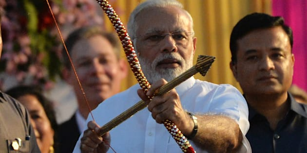 Indian Prime Minister Narendra Modi holds a bow and arrow at an event ahead of the burning of the effigy of the Hindu demon Ravana.