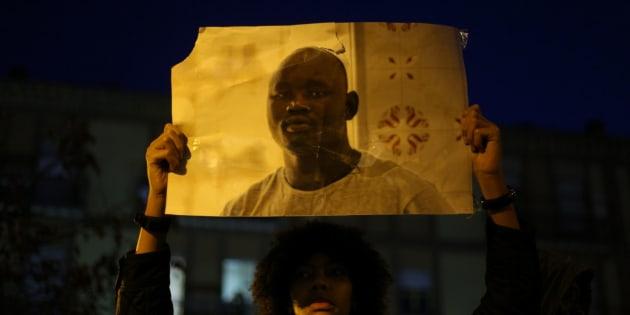 Una joven alza la foto de Mame Mbaye durante una concentración antirracista en Lavapiés.
