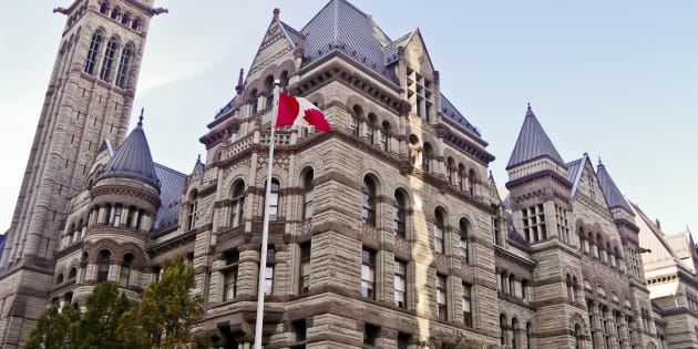 Old city hall of Toronto, Ontario, Canada with a Canadian flag and pole on the foreground.