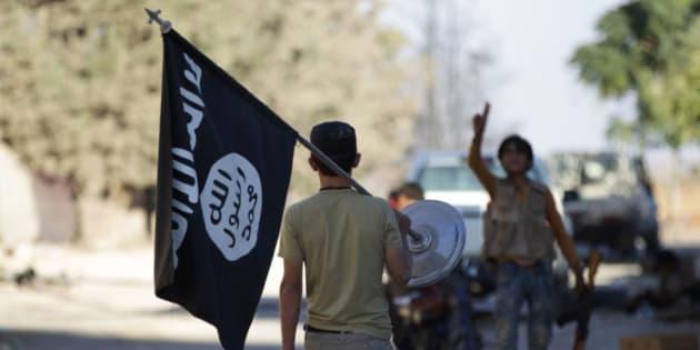 Un rebelde sirio se lleva como trofeo una bandera del ISIS de la villa de Akhtarin, al norte de Alepo (Siria), tras la retirada de los islamistas.