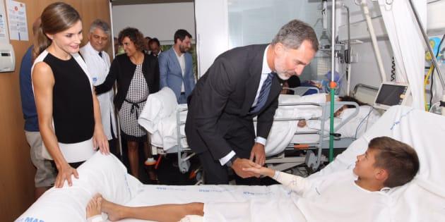 Los reyes Felipe y Letizia, saludando a uno de los niños heridos, en su visita al Hospital del Mar de Barcelona.
