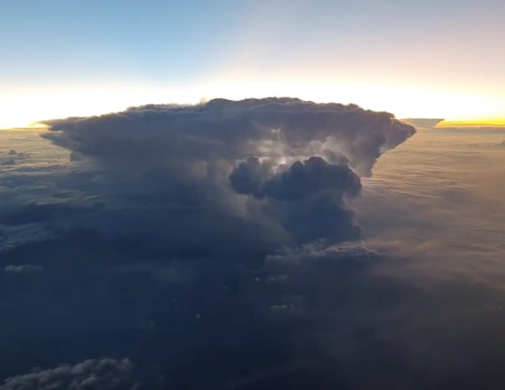Pilot films rare moment sun rises over thunderstorm