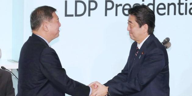 総裁選を終え、握手する安倍晋三首相(右)と石破茂元幹事長=20日午後、東京・永田町の同党本部