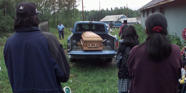 Family and friends watch as Cynthia Jane Keeper is taken to her resting place after a funeral service at the Jesus Name Church in Pikangikum, Ont. on July 23, 2001.