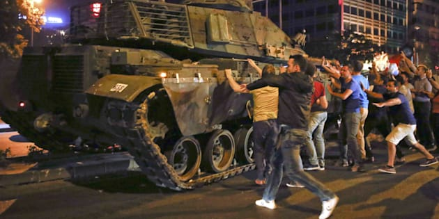 Ciudadanos turcos reaccionan al ver un tanque en las calles de Ankara, en la noche del intento de golpe.