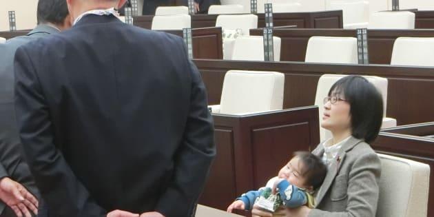 2017年11月、熊本市議会に生後7カ月の長男を抱いたまま出席し、議会事務局職員らによる退席要 請を拒否する緒方夕佳市議(右)=熊本市中央区
