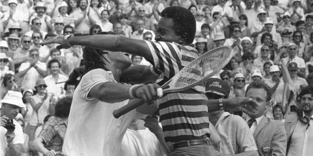 Yannick Noah et son père Zacharie Noah sur le court de tennis après sa victoire à Rolland Garros contre le Suédois Mats Wilander, le 5 juin 1983.
