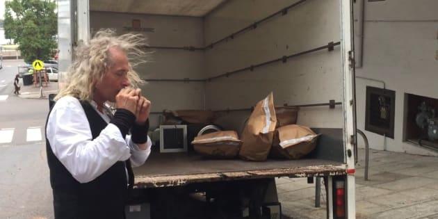 Paul Robert Burton plays music off equipment seized at the raid.