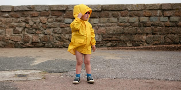 Young boy wearing a yellow jacket at the Engliash seaside, on a windy day.