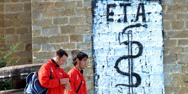 Imagen de archivo de dos personas pasando junto a una pintada de ETA en el pueblo vasco de Arbizu.