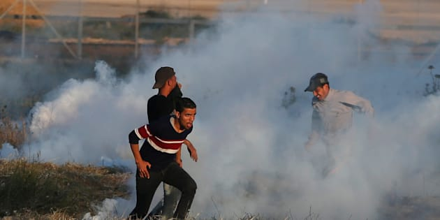 Palestinians run from tear gas, during clashes with Israeli troops at a protest, at the Israel-Gaza border, demanding the right to return to their homeland, east of Gaza City April 1, 2018. REUTERS/Mohammed Salem