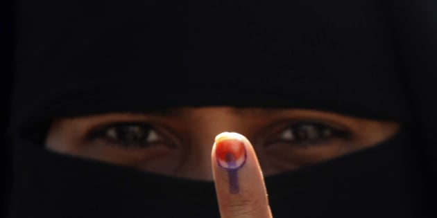 An Indian Muslim woman displays her finger after casting her vote in the first phase polling of Gujarat assembly elections on December 13, 2012 in Surat, India.