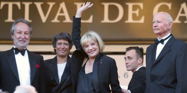 L'actrice Jeanne Moreau fait signe au public lors du 56ème festival de Cannes, entourée du Président Gilles Jacob (à droite), de la directrice générale du festival Véronique Cayla, et du Président d'Arte Jérôme Clément (à gauche), le 24 mai 2003.