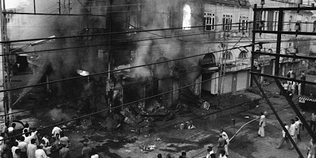 Indian bystanders look on as a building belonging to Sikh merchants burns in Daryaganj, New Delhi, in the wake of then Prime Minister Indira Gandhi's assassination.