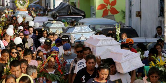 Un grupo de gente desfila por las calle de Atzala (Puebla) portando los ataúdes de varias víctimas del seísmo.