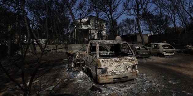 Vehículos destruidos frente a una casa dañada tras el incendio forestal en Mati, Grecia.