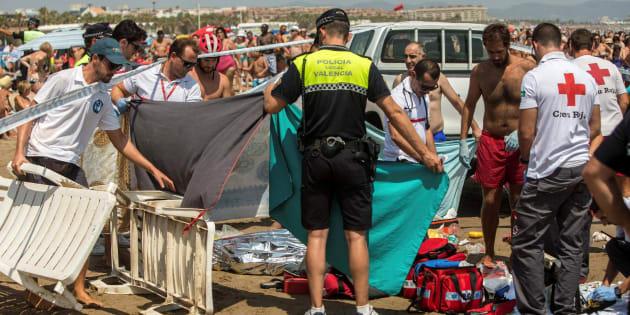 Miembros de la Cruz Roja y Policía Local, junto al cuerpo de un hombre que se ha ahogado en aguas de la playa de la Malvarrosa, en Valencia.