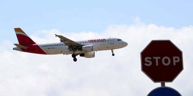 Un avión de Iberia vuela sobre una señala de stop al acercarse al aeropuerto de El Prat en Barcelona.