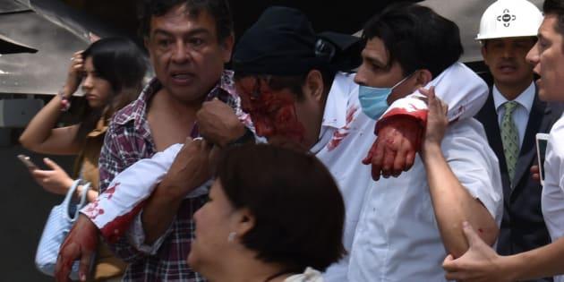 Varias personas ayudan a los heridos tras el terremoto en México.