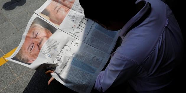 Un hombre lee un periódico con la noticia entre Trump y Kim Jong-Un.