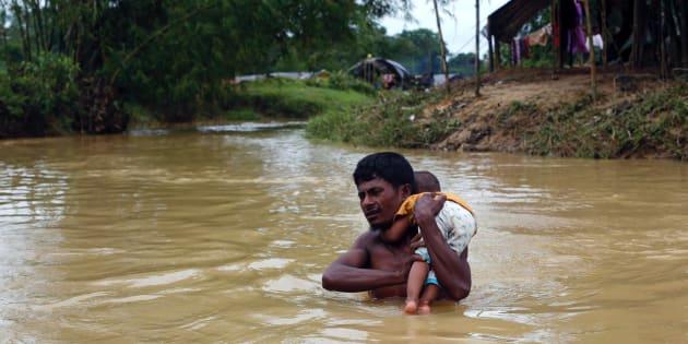 Un refugiado rohingya cruza un río con un bebé en brazos en Cox's Bazar, Bangladés, el 18 de septiembre de 2017.