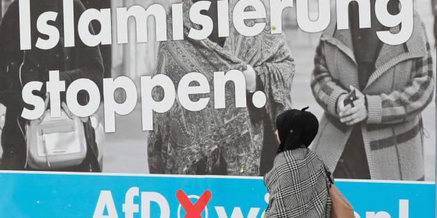 Una mujer cubierta con un pañuelo pasa por delante de un cartel electoral del partido extremista anti-inmigración Alternative für Deutschland (AfD) en Marxloh, un barrio de Duisburg con mucha población de origen turco. 13 de septiembre de 2017.