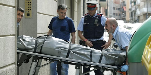 Operarios retiran el cuerpo sin vida de la mujer de 78 años que ha sido supuestamente asesinada por su marido.