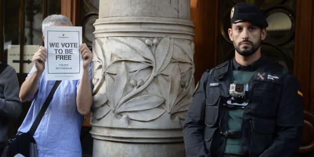 Un hombre sostiene un cartel proreferéndum junto a un agente de la Guardia Civil frente a la Consellería de Economía.