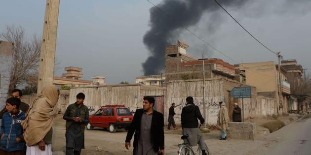 Civiles afganos en las inmediaciones del lugar del ataque, donde se eleva una columna de humo.