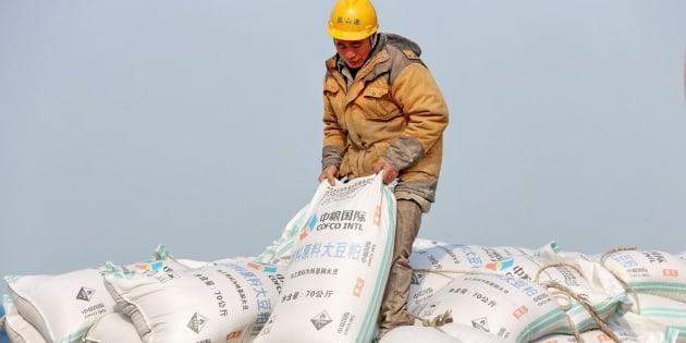 Un trabajador chino carga un saco de cereales.