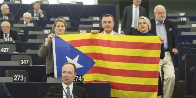Eurodiputados posan con una bandera estelada durante el debate en el Parlamento Europeo.