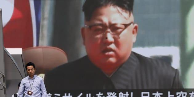Los peatones caminan bajo un monitor a gran escala que muestra al líder norcoreano Kim Jong-un.